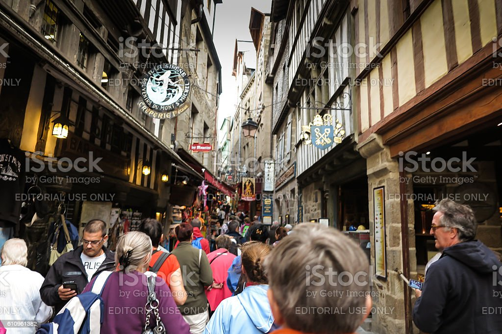 Unidentified tourists in commercial part of the Mont Saint Michel stock photo
