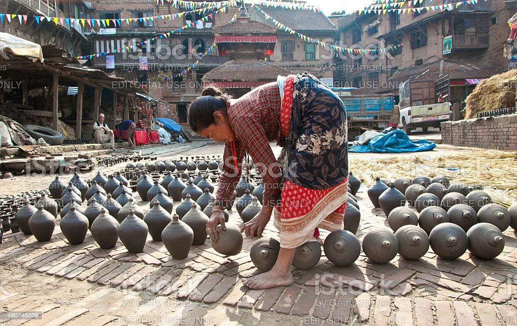 Unidentified woman is molding the pot in Bhaktapur, Nepal. stock photo