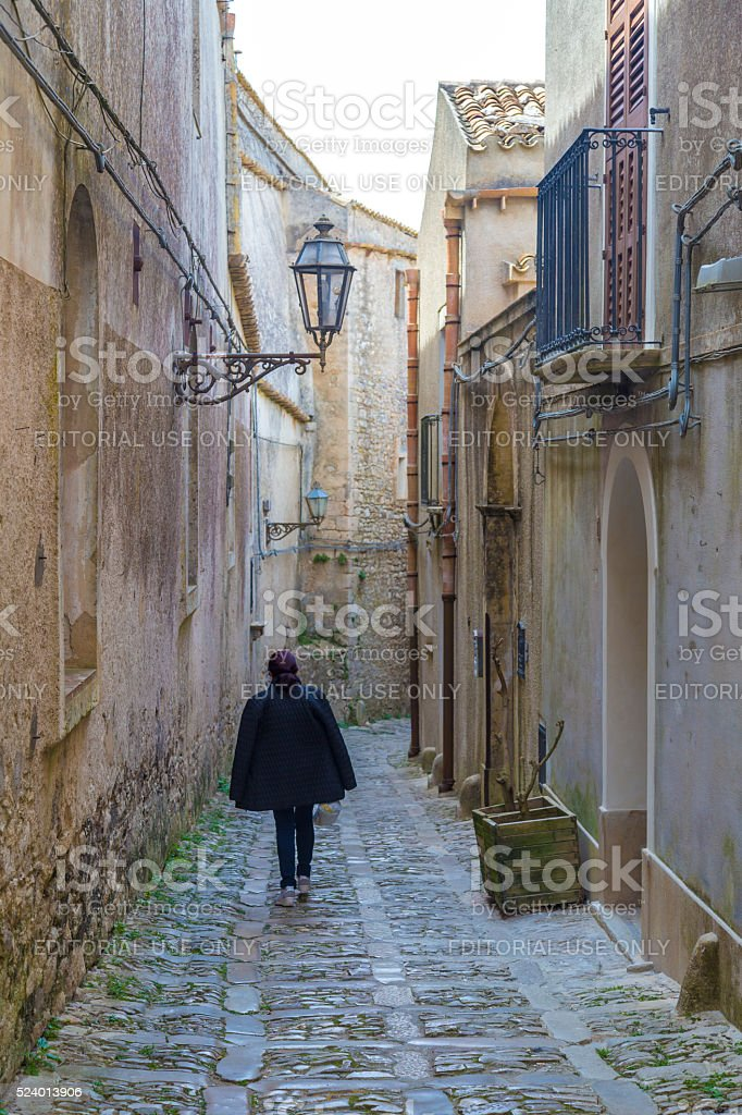Unidentified woman walking away in ancient, typical stock photo