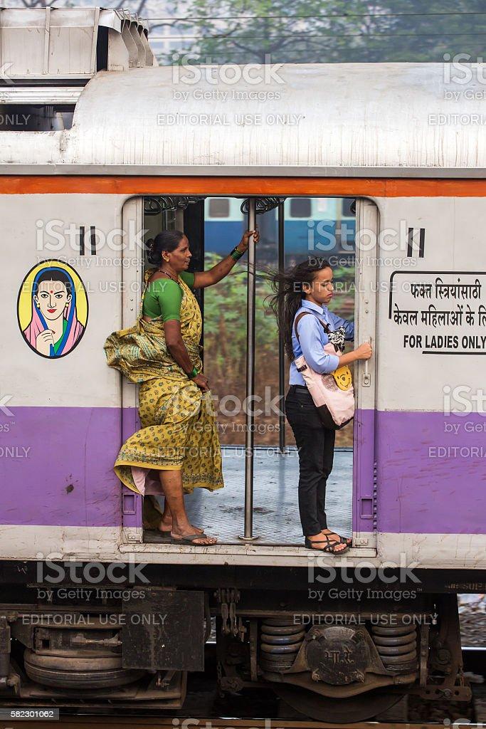 Unidentified women traveling via Suburban train in Mumbai, India. stock photo