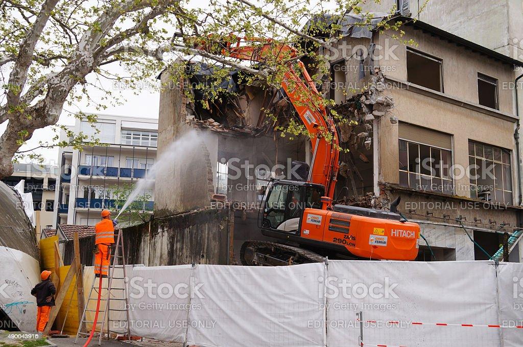 Unidentified workers demolish Building in Bellinzona,Switzerland. stock photo