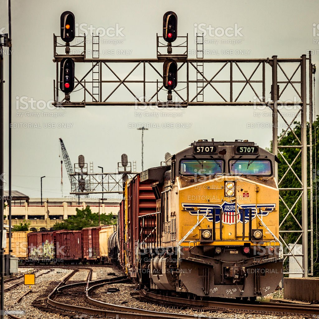 Union Pacific (UP) freight train passing under city signal gantry stock photo