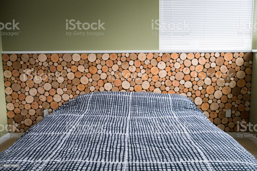Headboard made of wood discs cut from alder logs and stained