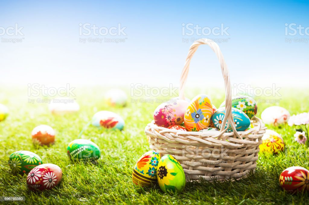 Unique hand painted Easter eggs in basket and lying on grass, blue sky stock photo