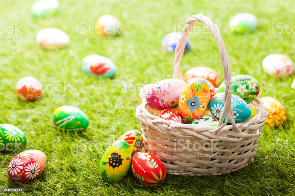 Unique hand painted Easter eggs in basket on grass stock photo