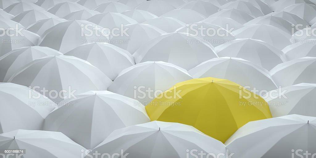 Unique yellow umbrella among many dark ones. stock photo