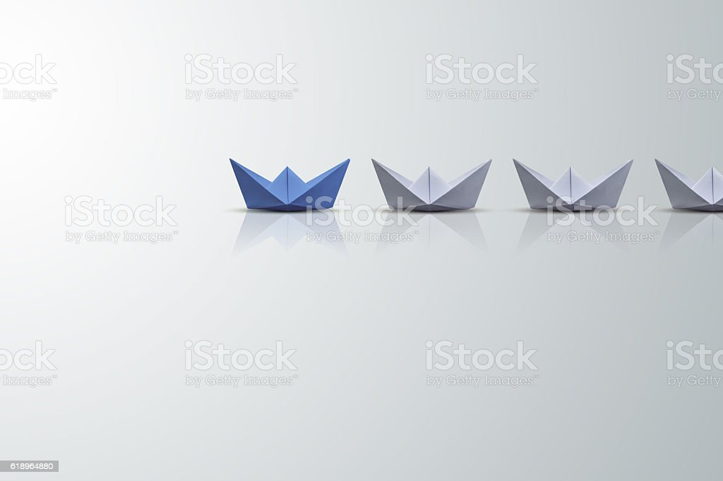 uniqueness concept, paper boat outstanding from the others stock photo