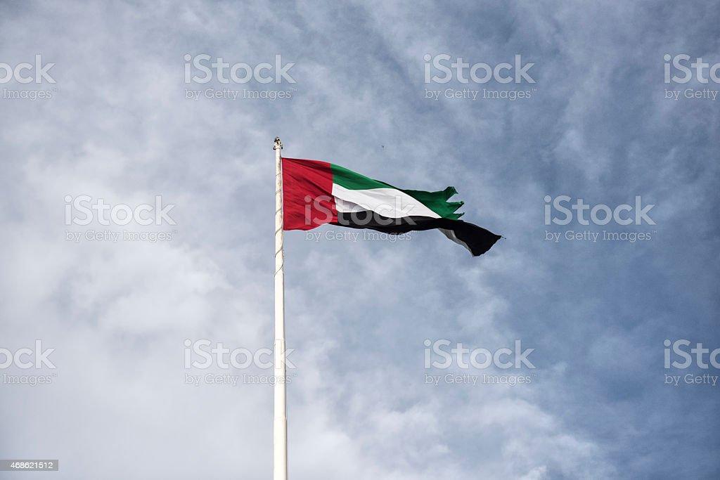 United Arab Emirates flag against a cloudy blue sky stock photo
