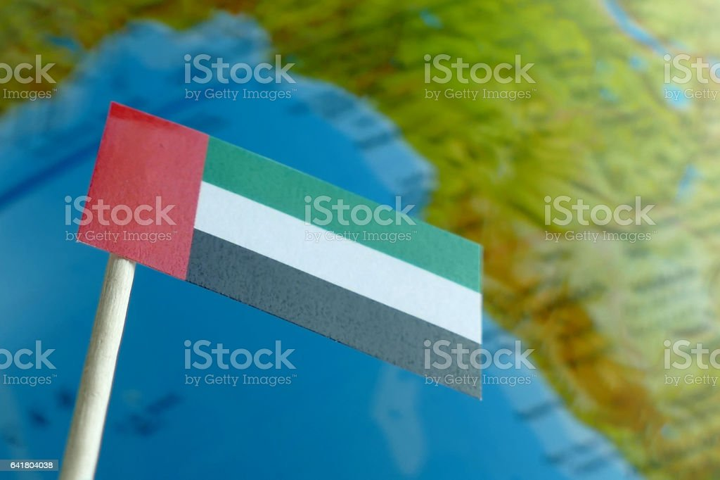 United Arab Emirates flag with a globe map as background stock photo