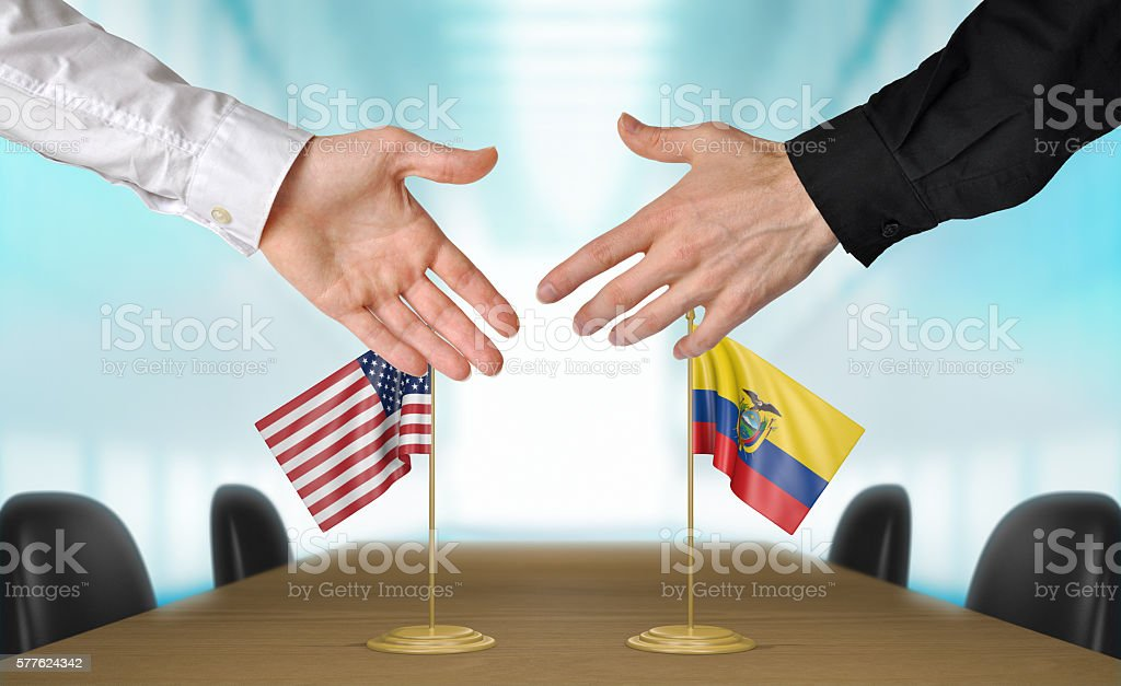 United States and Ecuador diplomats shaking hands to agree deal stock photo