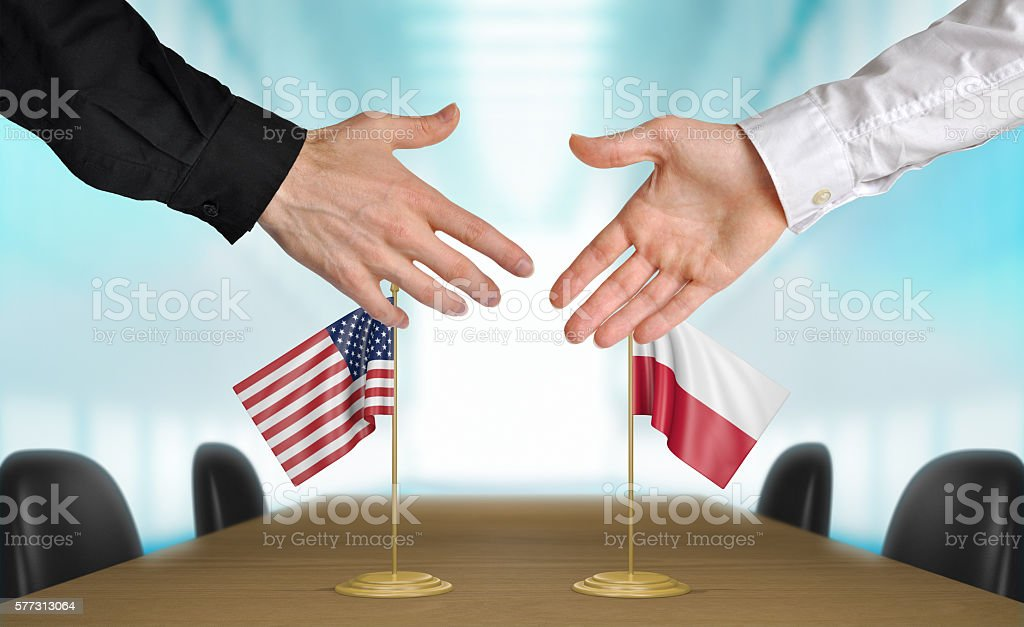 United States and Poland diplomats shaking hands to agree deal stock photo