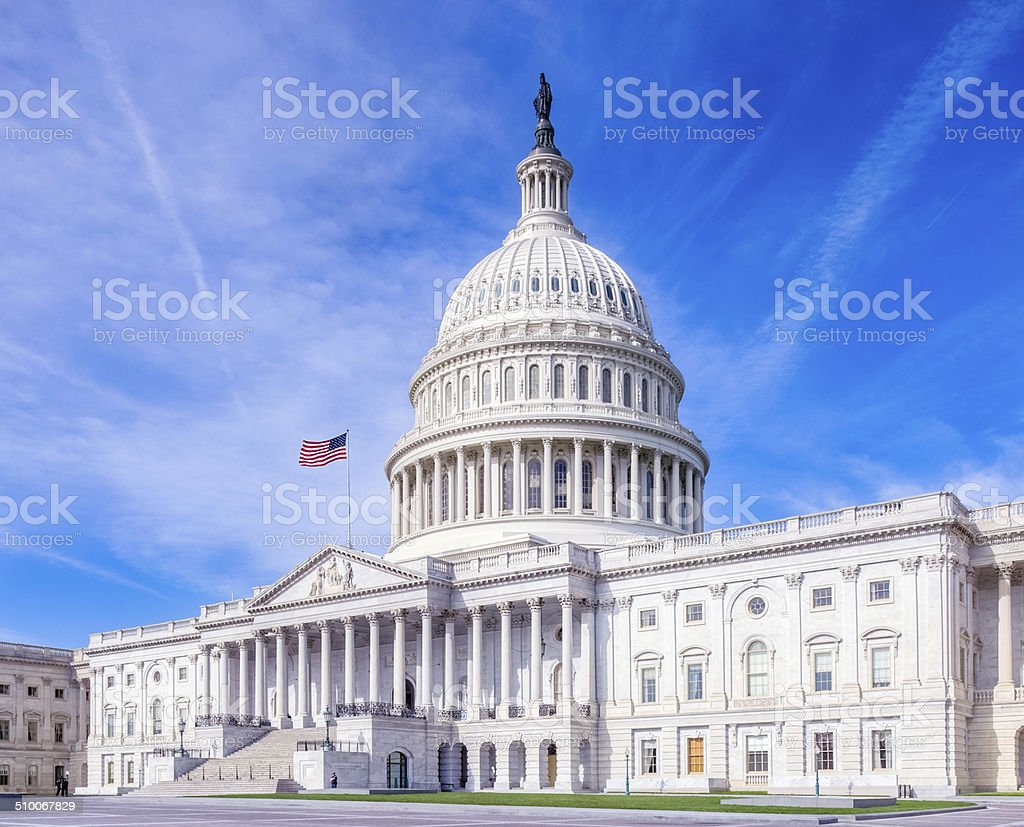 United States Capitol with American Flag Under Brilliant Sky stock photo