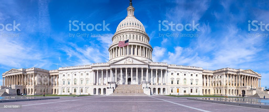 United States Capitol with Flag Flying under Blue Sky stock photo