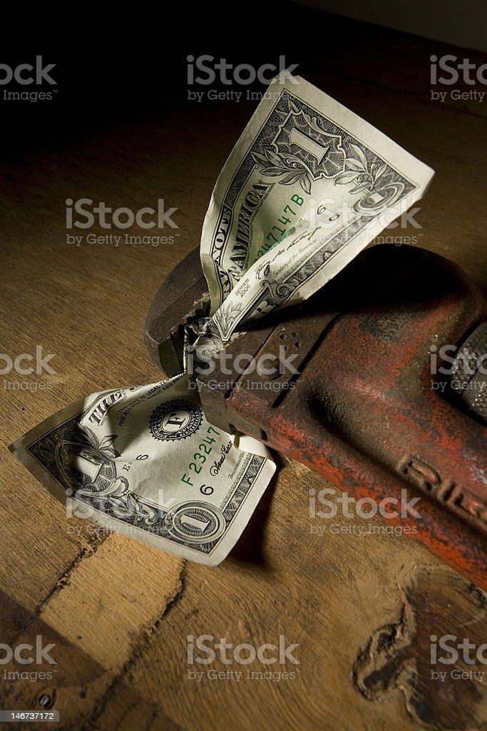 United States Dollar Bill crunched in a pipe wrench royalty-free stock photo
