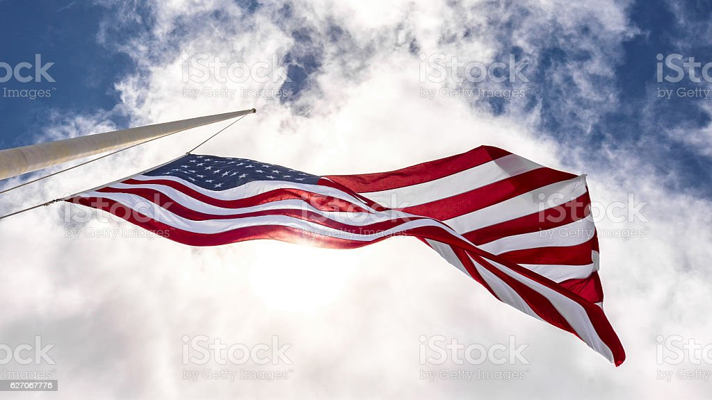 United States flag at half mast, looking up with sun stock photo