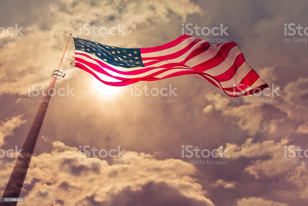 United States flag blows in the wind stock photo