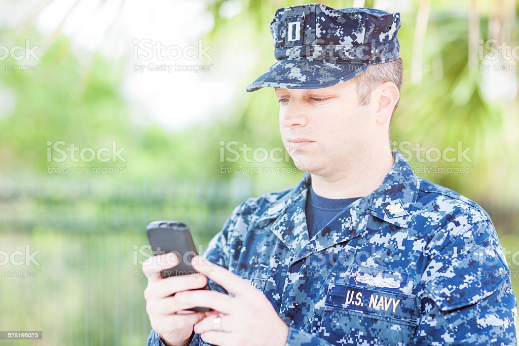 United States Naval Lieutenant Texting on Smart Phone stock photo