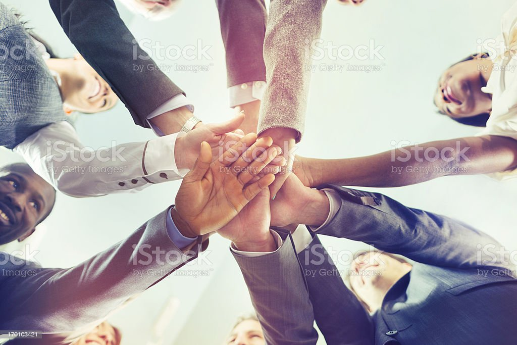 Unity of successful multi-ethnic business people holding hands stock photo