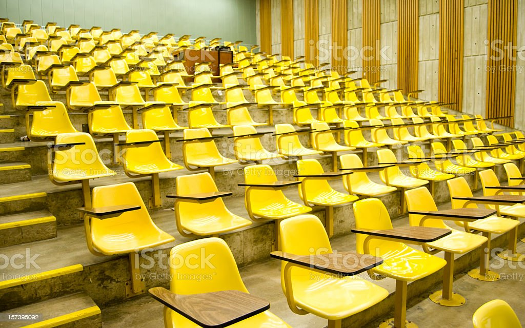 University lecture hall with yellow chairs and wood tables royalty-free stock photo