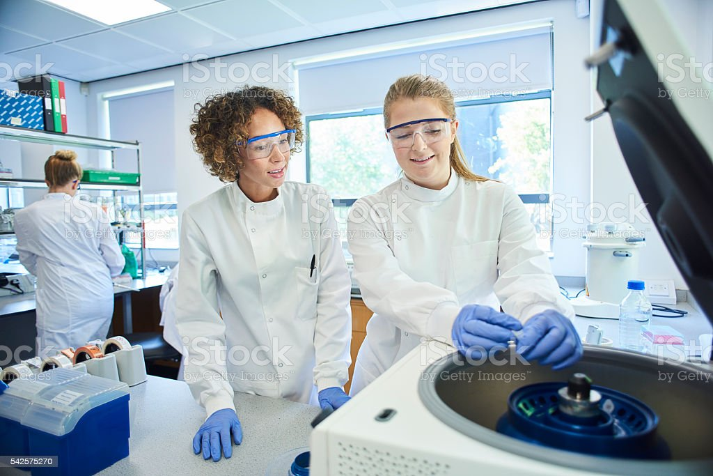university student and lecturer loading a centrifuge stock photo