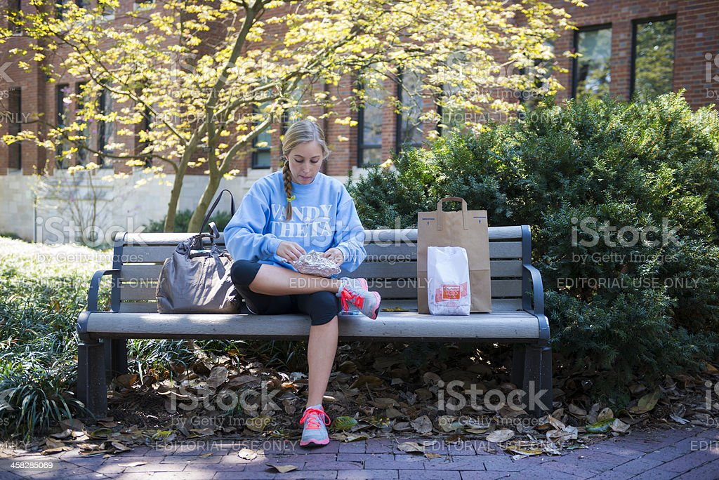 University student eating lunch on campus stock photo