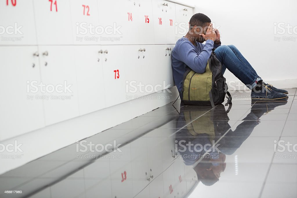 University student sitting alone with his hands on face stock photo