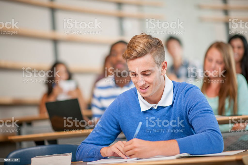 University Student Taking Notes in Class stock photo
