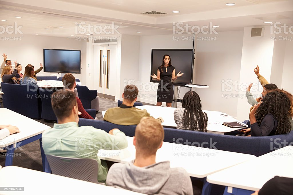 University students study in classroom with female lecturer stock photo