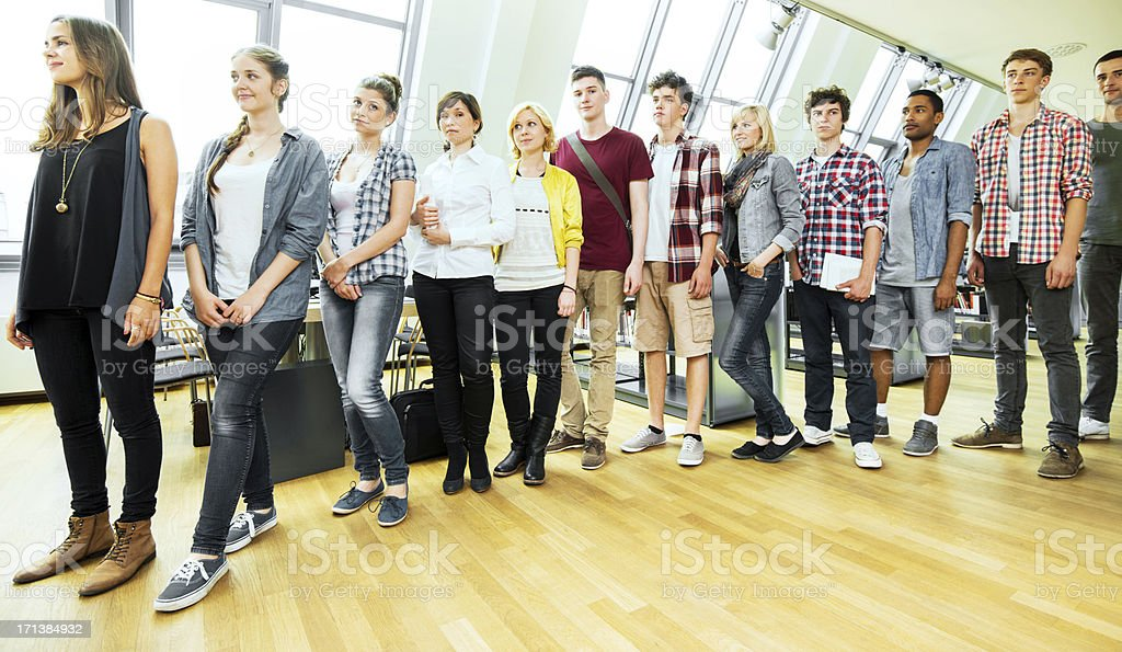 University students waiting in line to take books. stock photo