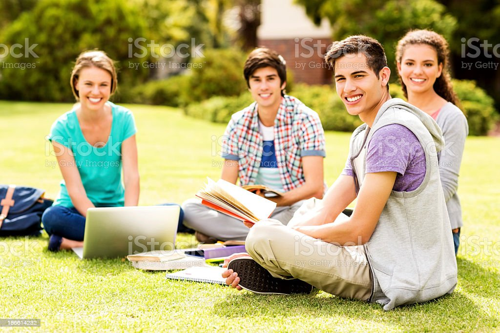 University Students With Laptop And Books Sitting On Campus royalty-free stock photo