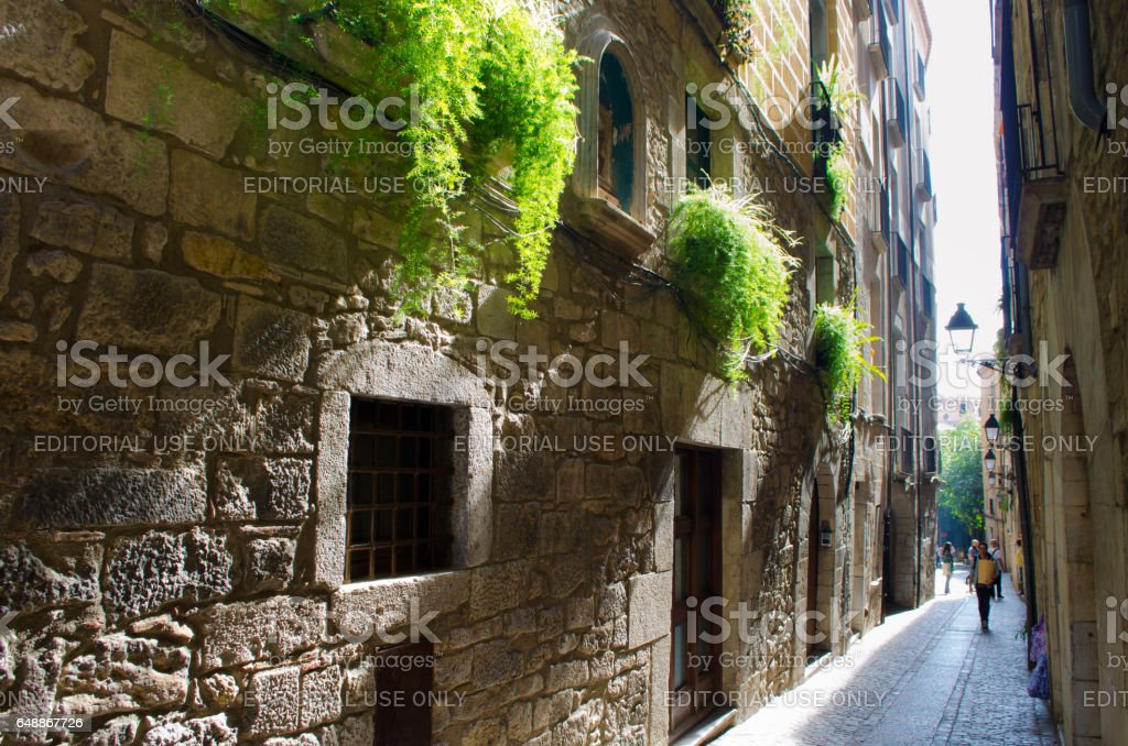 GIRONA - OCTOBER 21: Unknown people on city streets. City architecture. Shooting in an ancient part of the city. Girona on October 21, 2013, Spain. stock photo