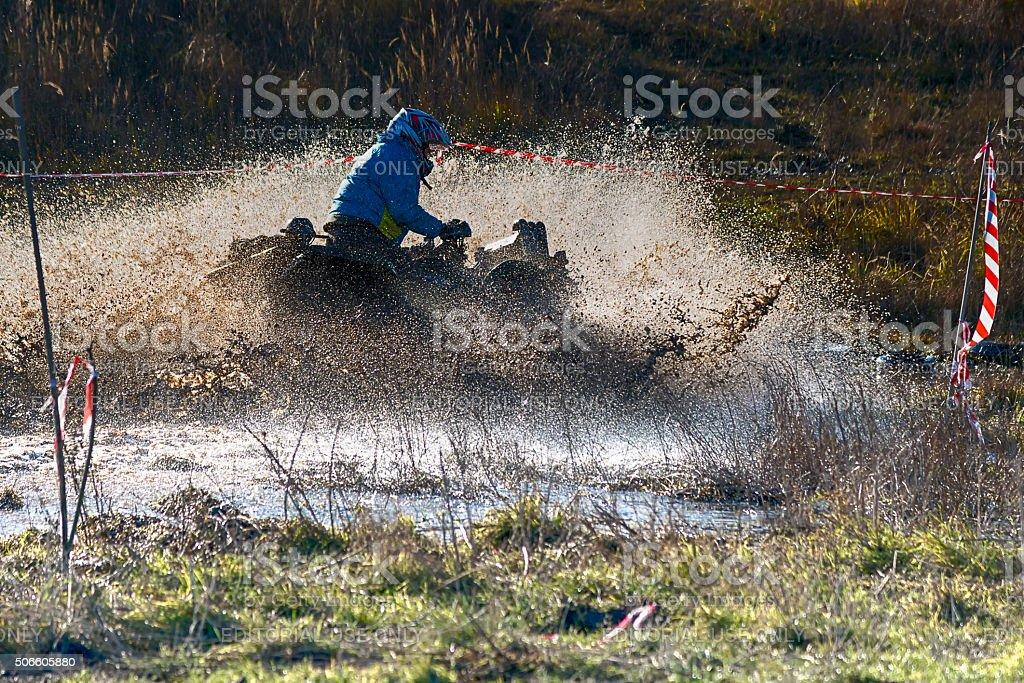 Unknown rider on ATV overcomes a water barrier stock photo