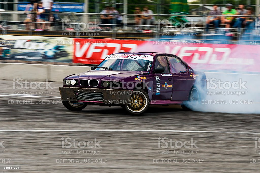 Unknown rider on the car brand BMW overcomes the track stock photo