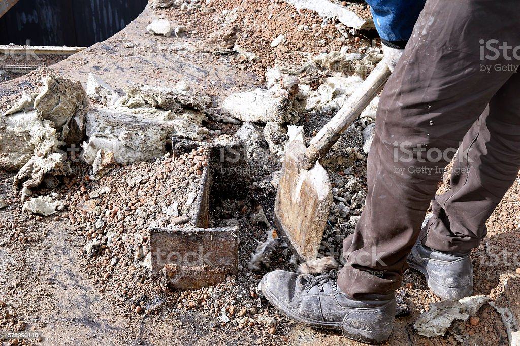 Unknown worker with a shovel clearing construction debris stock photo