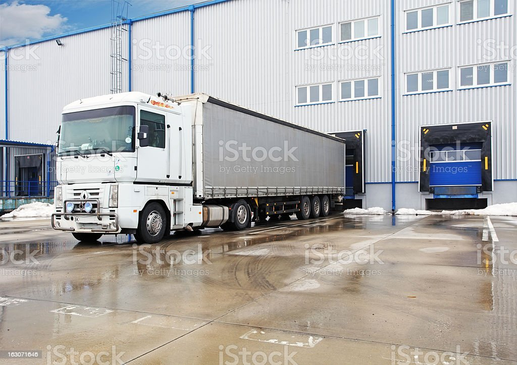 Unloading big container trucks at warehouse building royalty-free stock photo
