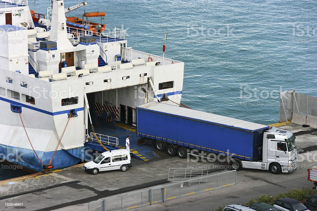 Unloading cargo from the ship to a truck stock photo