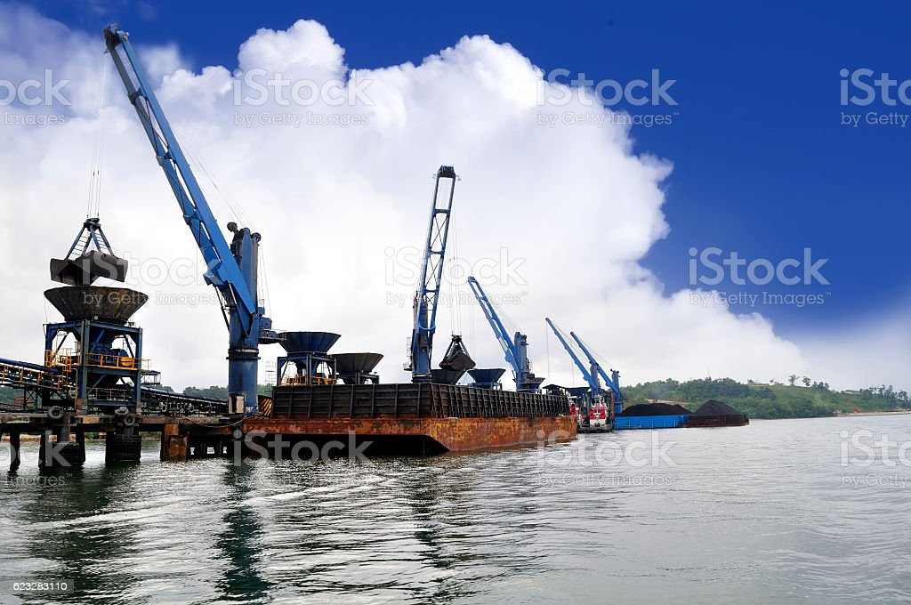 unloading coal from barge to hopper at the coal port stock photo