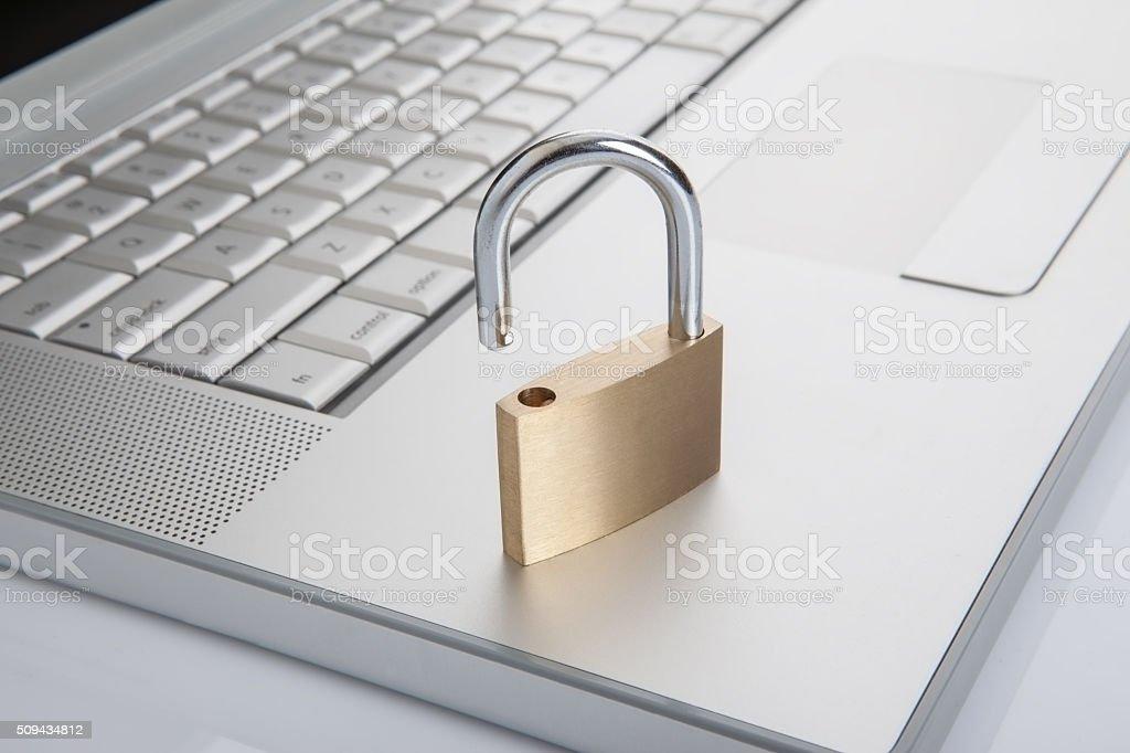 Unlock padlock standing on laptop stock photo
