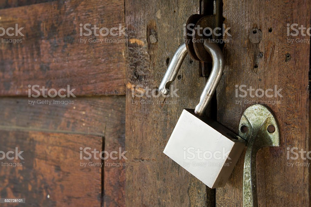 unlocking padlock  on a wooden door stock photo