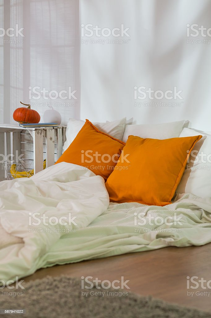 Unmade bed in modest room stock photo
