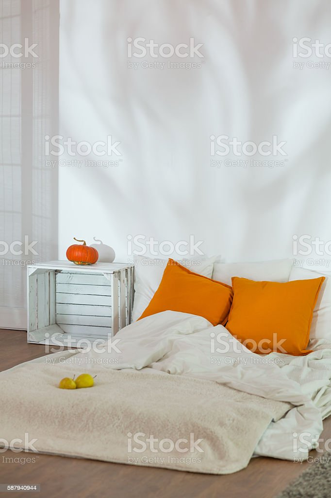 Unmade bed in simple autumn bedroom stock photo