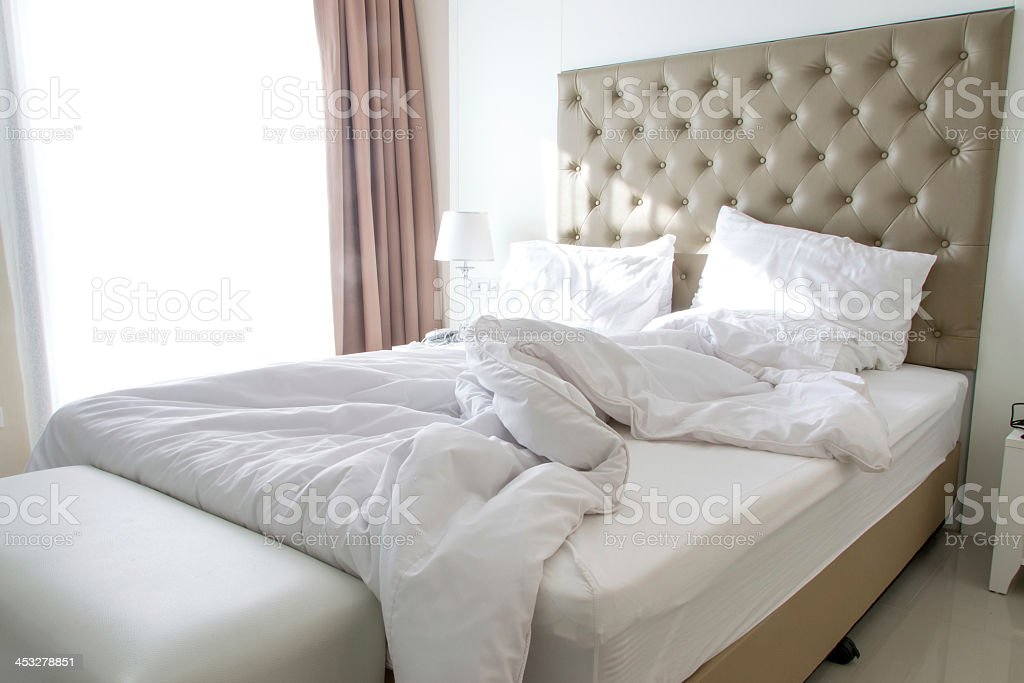 Unmade bed on a modern bedroom in light colors stock photo