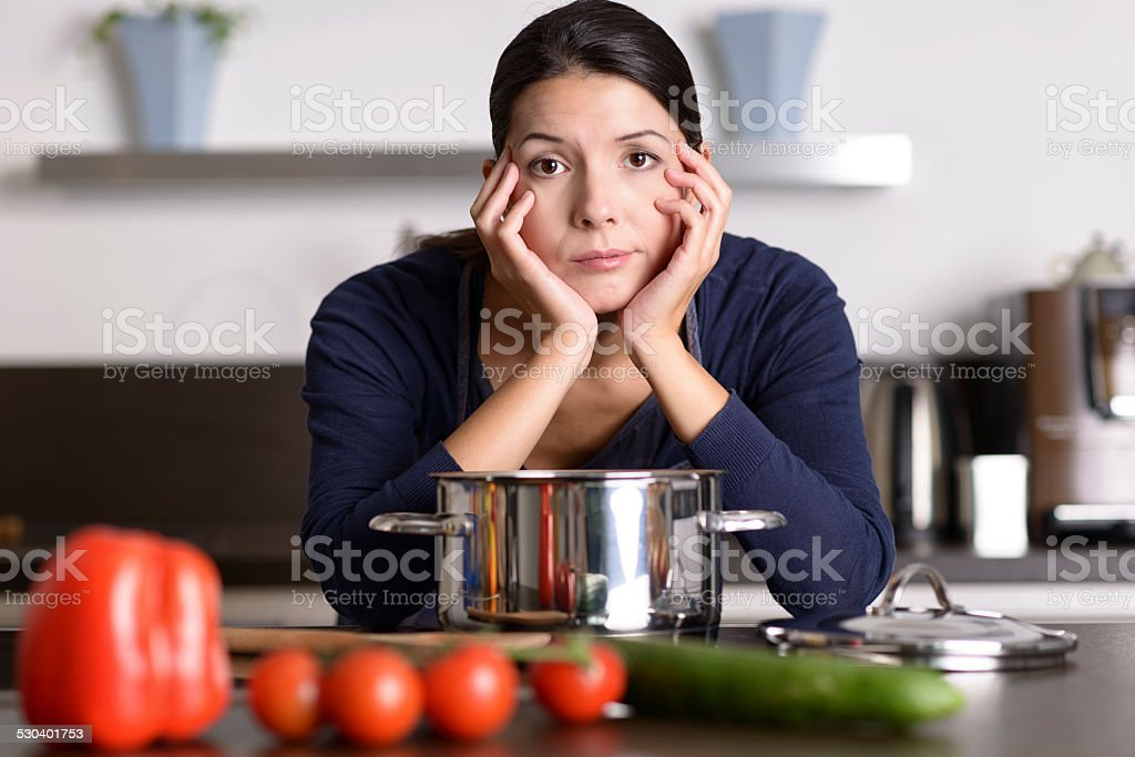 Unmotivated woman preparing the dinner stock photo