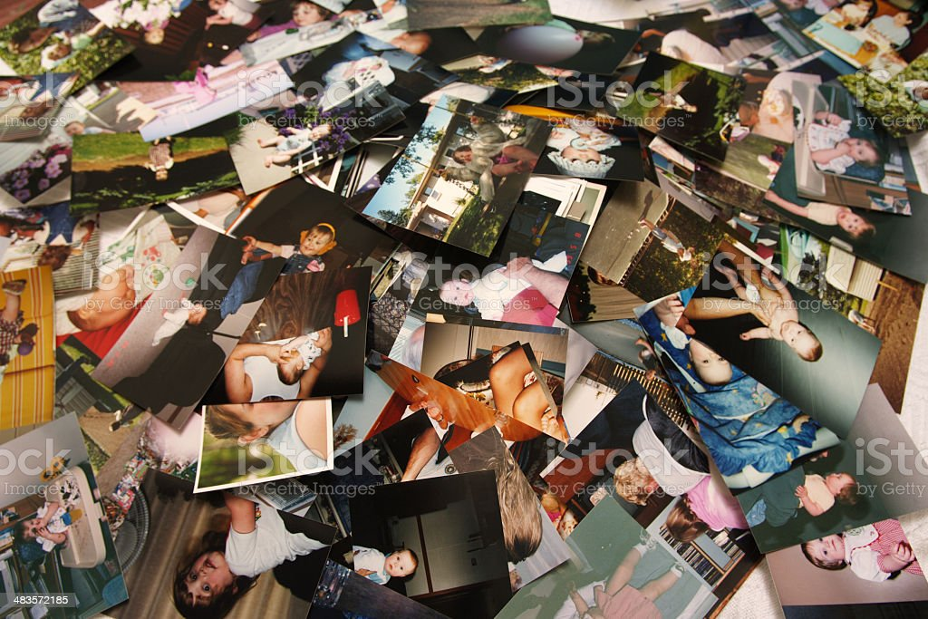 Unorganized pile of photographs of a little girl's life stock photo