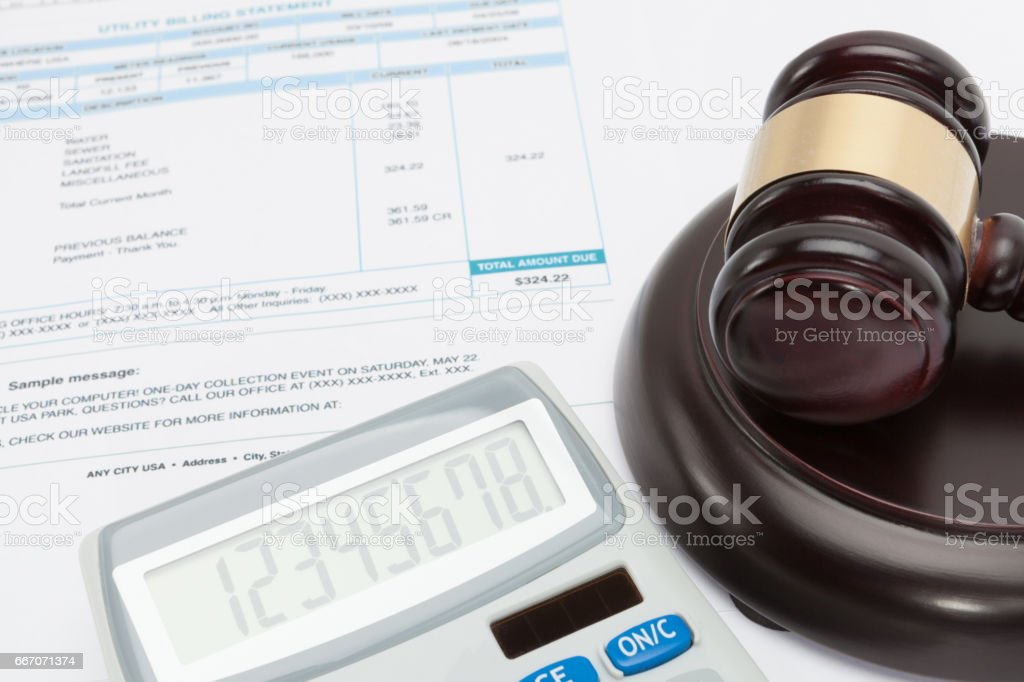 Unpaid bill with calculator and wooden gavel over it series stock photo