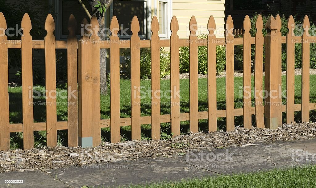 Unpainted, wooden fence separating yard and sidewalk.  royalty-free stock photo