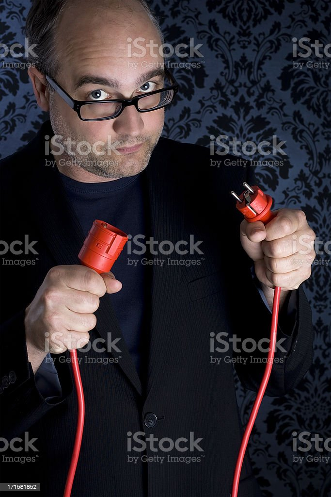 Unplugged. Bald middle-aged man holding two red plug connectors royalty-free stock photo