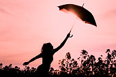 Unplugged free silhouette woman with umbrella fly to future