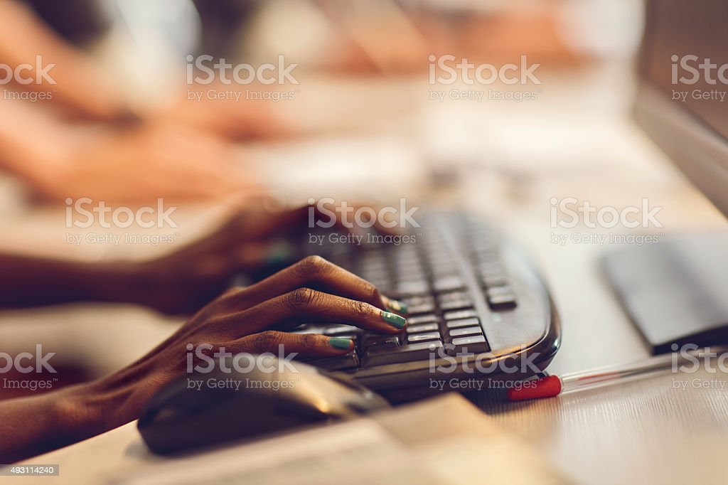 Unrecognizable African American person typing on computer keyboard. stock photo