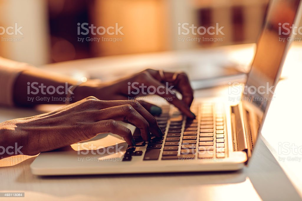 Unrecognizable African American person typing on laptop keyboard. stock photo